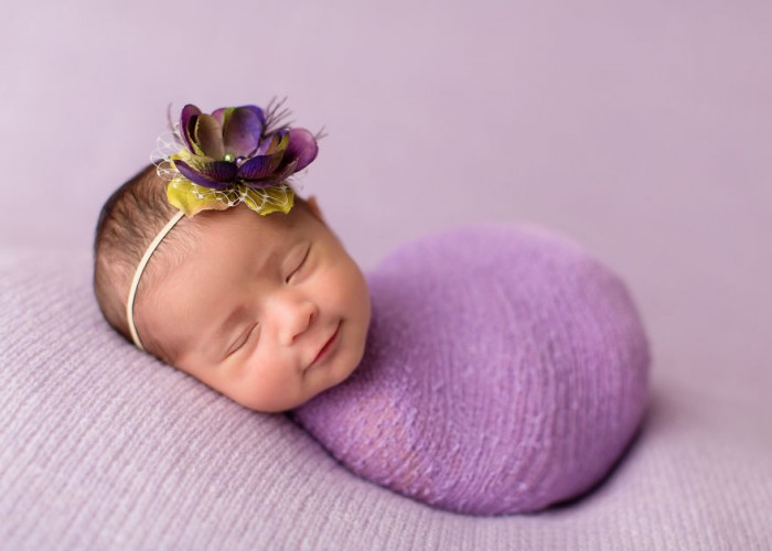 A photo of a baby smiling in her sleep.
