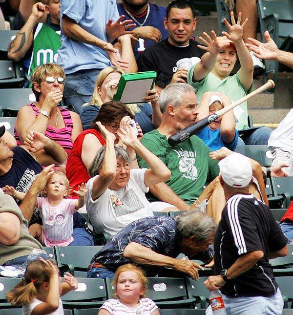 perfectly timed photos, a man got hit by the baseball bat during the game