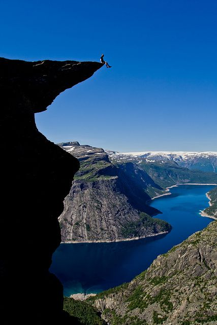 A fearless man sitting on Trolltunga rock is not afraid of heights.