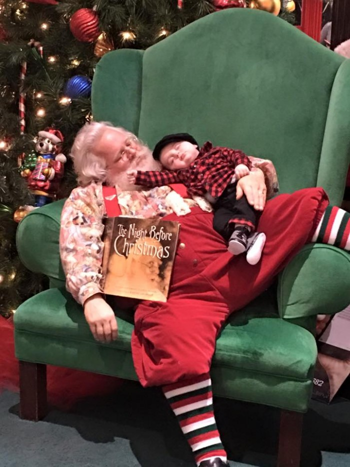 Cute little baby fell asleep while waiting to meet Santa.
